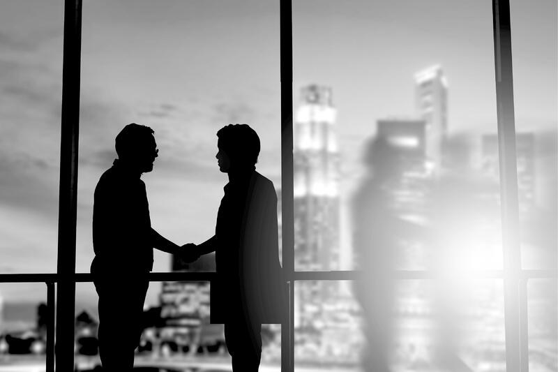 silhouette of two marketers shaking hands in front of office building window