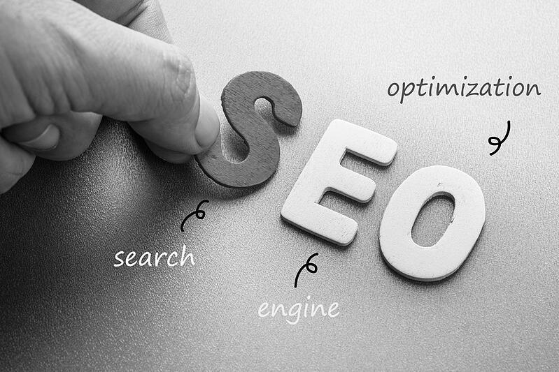 person placing letters for SEO search engine optimization on a table