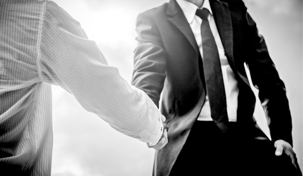 two marketers wearing suits shaking hands