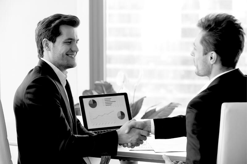 two smiling businessmen in suits shaking hands after sales meeting