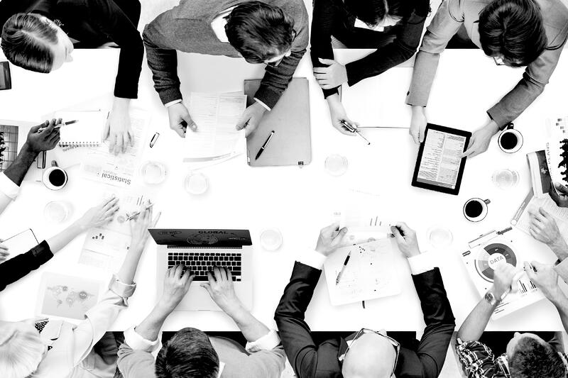 overhead view of group of workers at a desk brainstorming ideas with laptops and notepads