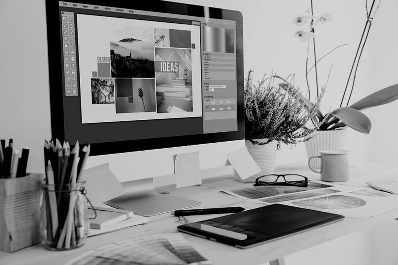desktop computer screen on desk displays graphic design template for websites