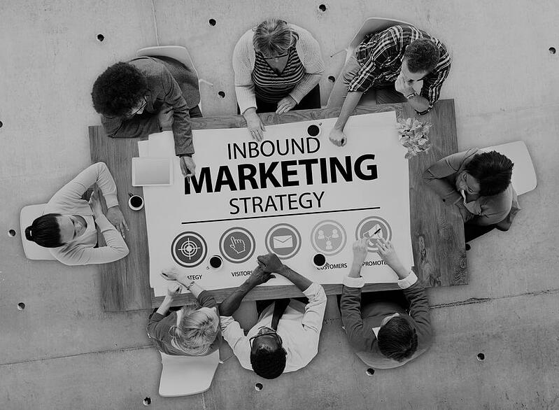 overhead view of group of marketers sitting around a table with inbound marketing strategy in the middle