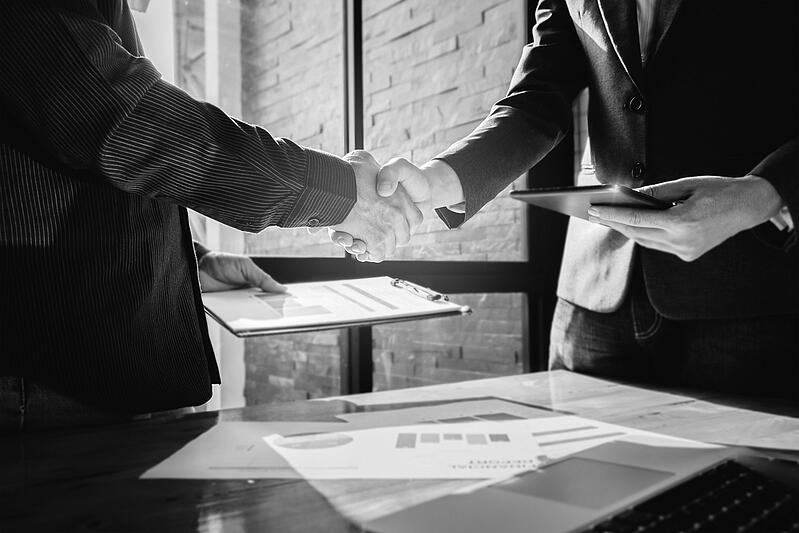 two marketing businessmen shaking hands in front of window