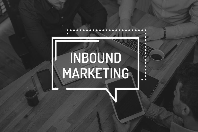 inbound marketing message over desk with marketers on tablet, laptop, and notebook