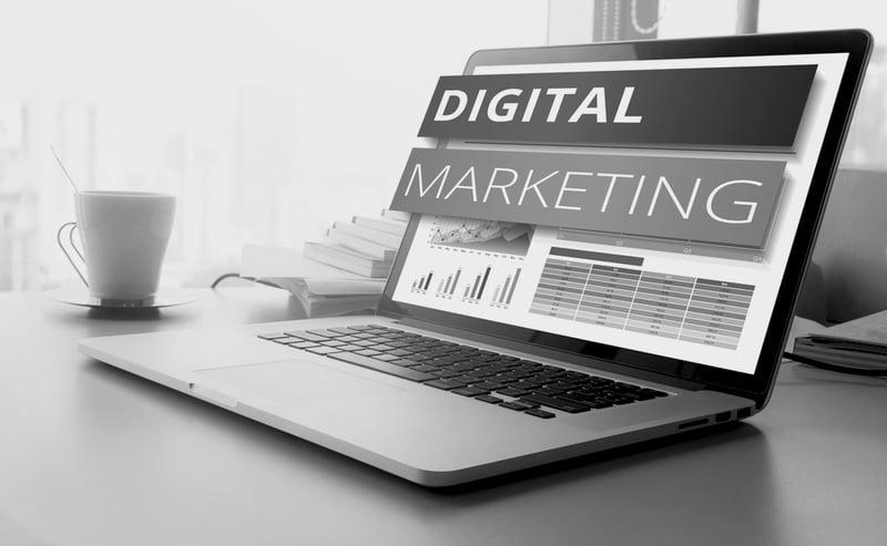laptop screen on desk displays digital marketing