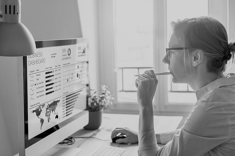 marketing woman with glasses and pen reviewing website performance analytics on computer