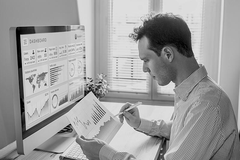 marketer reviewing metrics report and data on paper and computer screen