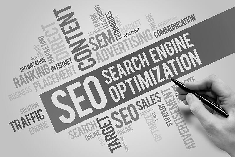 hand with pen writing about SEO search engine optimization