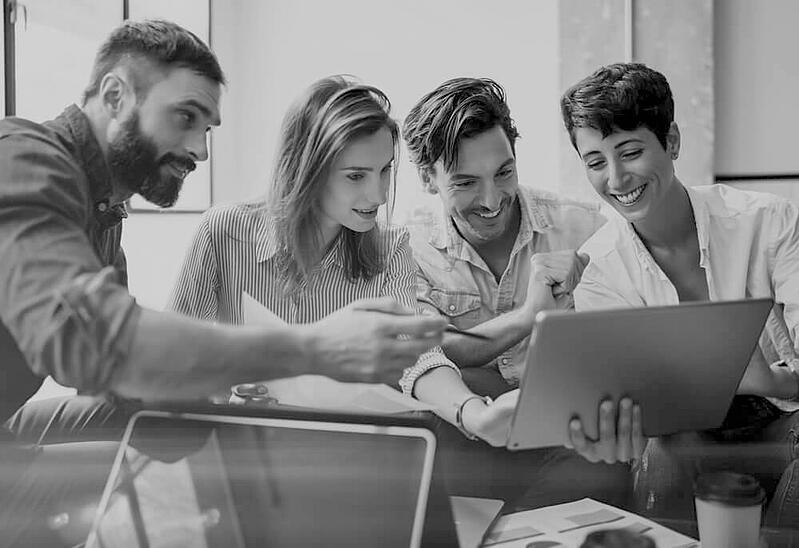 group of four excited and smiling marketers looking at a laptop screen together at an office desk