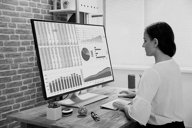businesswoman at wooden desk on large desktop computer with marketing metrics on screen