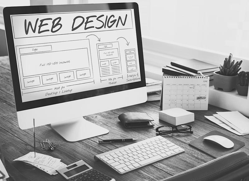 computer screen on desk displays website design outline for 2019