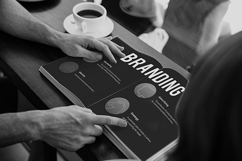 person pointing at branding book on desk with coffee cup