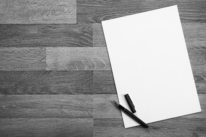 blank piece of paper with a pen on a wooden desk