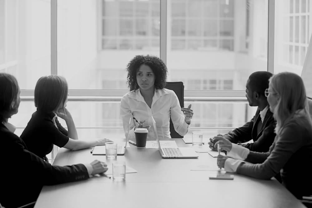 African American business woman leading team meeting at desk in front of a large window