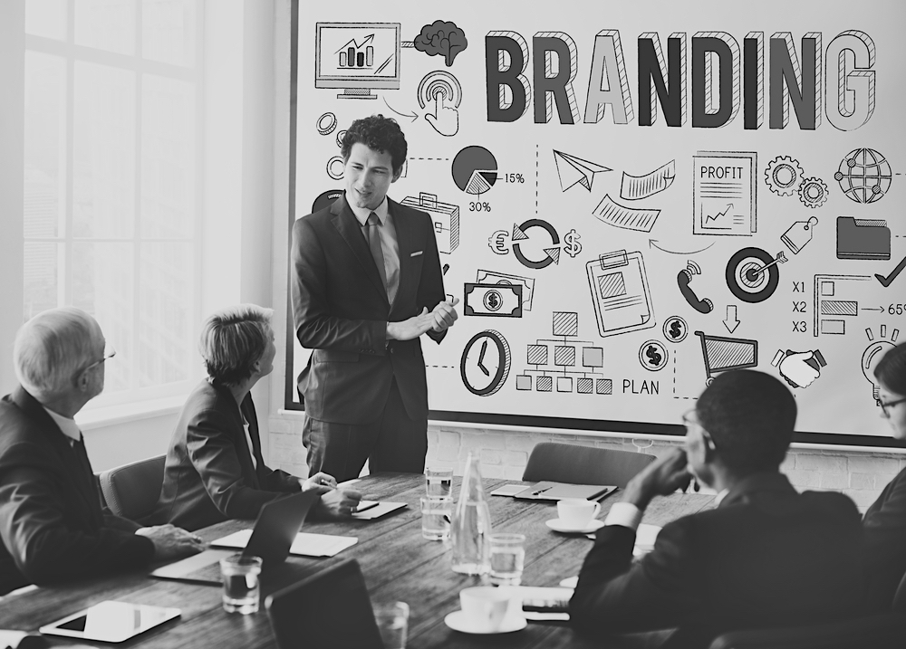 business man giving branding presentation on a white board to team of marketers sitting at a desk