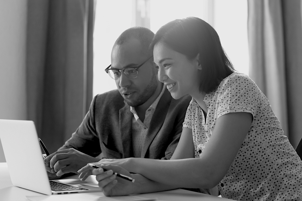 Asian-American woman and African-American man in front of laptop on desk