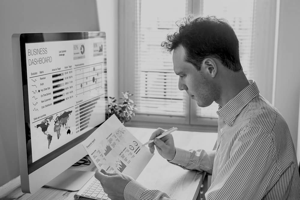 man at desk holding paper with website data in front of computer screen with a business dashboard and analytics