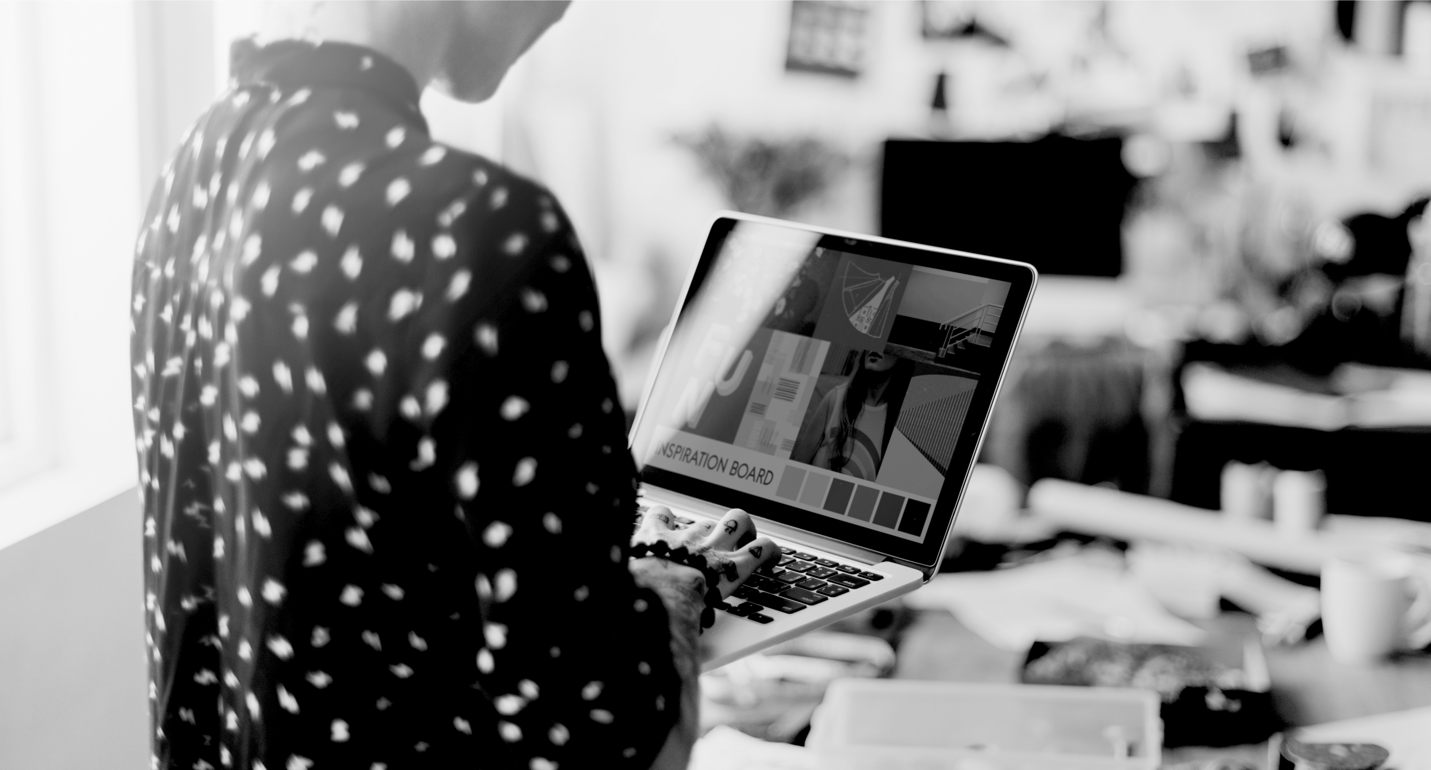 Web designer standing in office with laptop in hand
